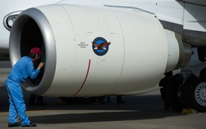 A maintenance worker inspects a Pratt & Whitney engine